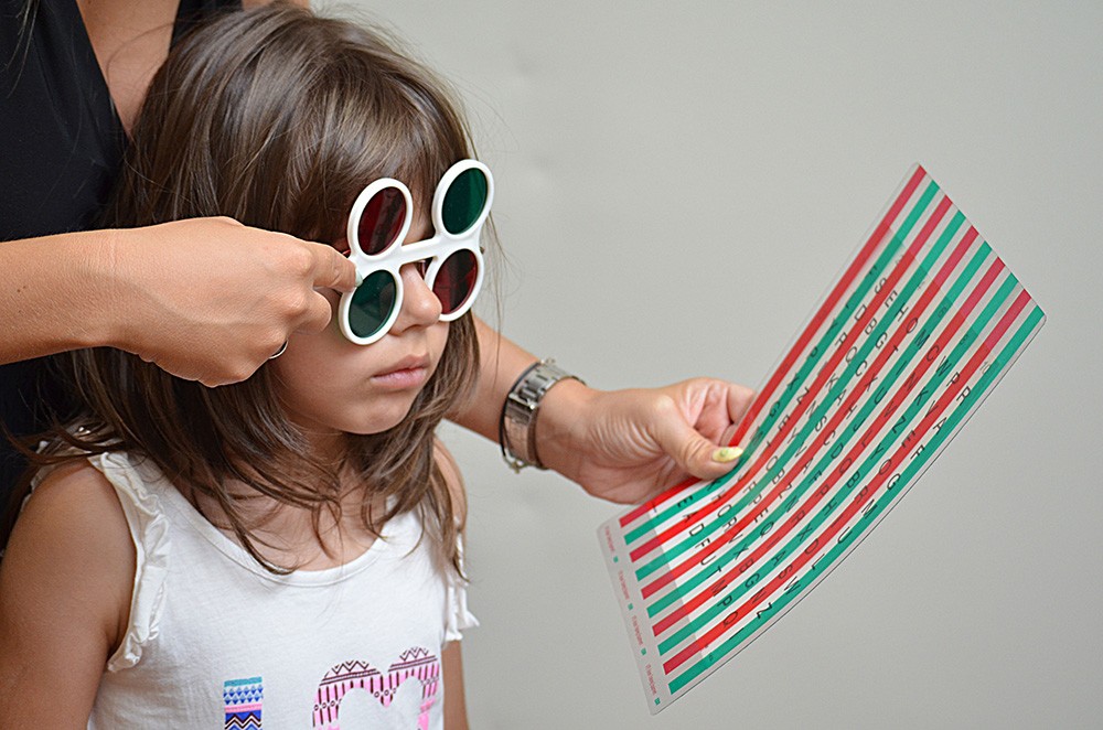 child doing vision therapy with red green glasses